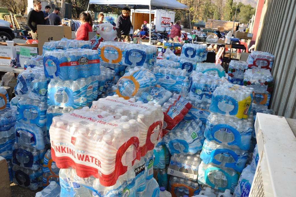 Shoulder-high stacks of bottled water sit outside the Stagecoach Station convenience store in Upper Ojai. The store has become a community hub and host to an ad-hoc relief station neighbors established in the wake of the Thomas Fire.