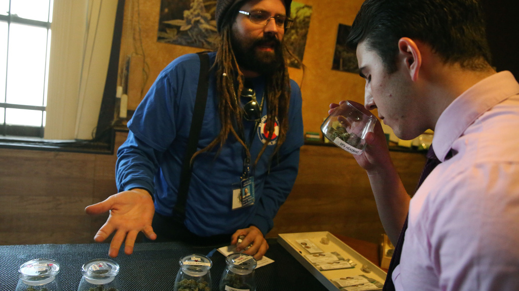 A customer smells a strain of marijuana while being helped by employee Billy Archilla inside the retail marijuana shop at 3D Cannabis Center, in Denver.