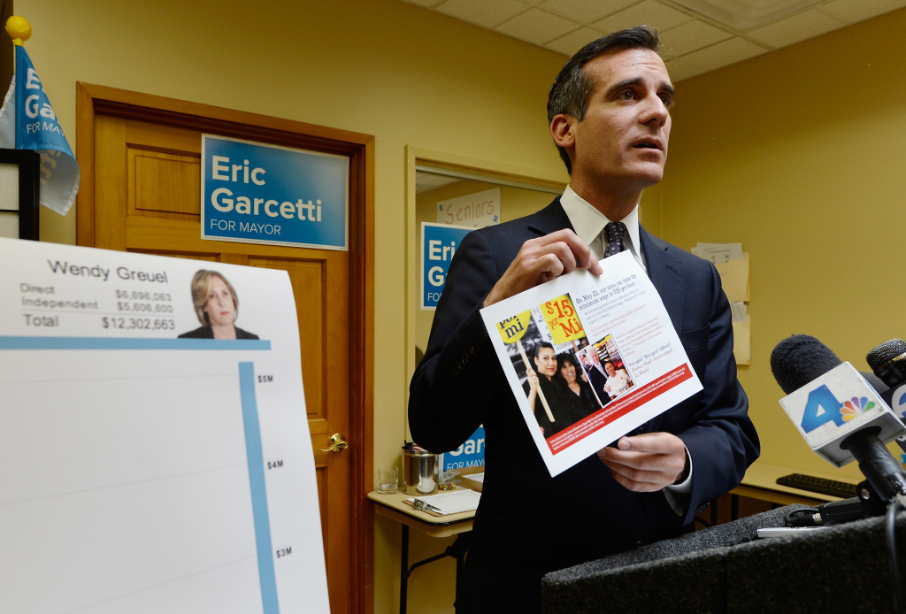 Los Angeles mayoral candidate and City Councilman Eric Garcetti holds a union sponsored campaign flier, which is being distrubuted in the poor Latino neighborhoods of Los Angeles telling voters that Los Angeles mayoral candidate Wendy Greuel would raise the minimum wage to $15 per hour if elected mayor, standing next to a chart showing total cointributions for both candidates during a news conference on May 13, 2013 in Los Angeles, California.