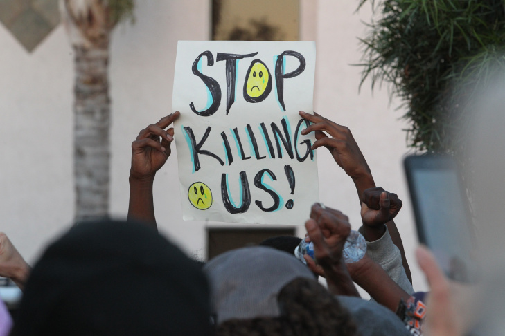 A man stands behind a picture of Alfred Olango during a protest Wednesday, Sept. 28, 2016, in El Cajon, Calif. Dozens of demonstrators on Wednesday protested the killing of Olango, shot by an officer after authorities said he pulled an object from a pocket, pointed it and assumed a