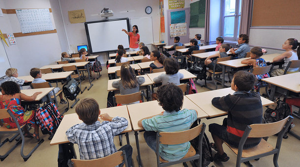 A teacher welcomes pupils in a classroom at David Johnston primary school on September 4, 2012.