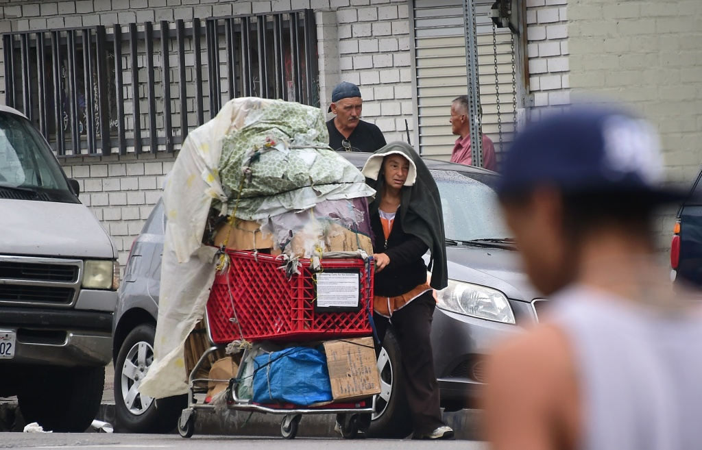 A homeless woman pushes her cart full of belongings along a street in Los Angeles, California.