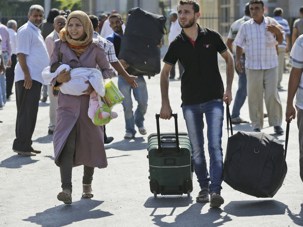 Syrian refugees pass through the Turkish Cilvegozu gate border on Sunday.