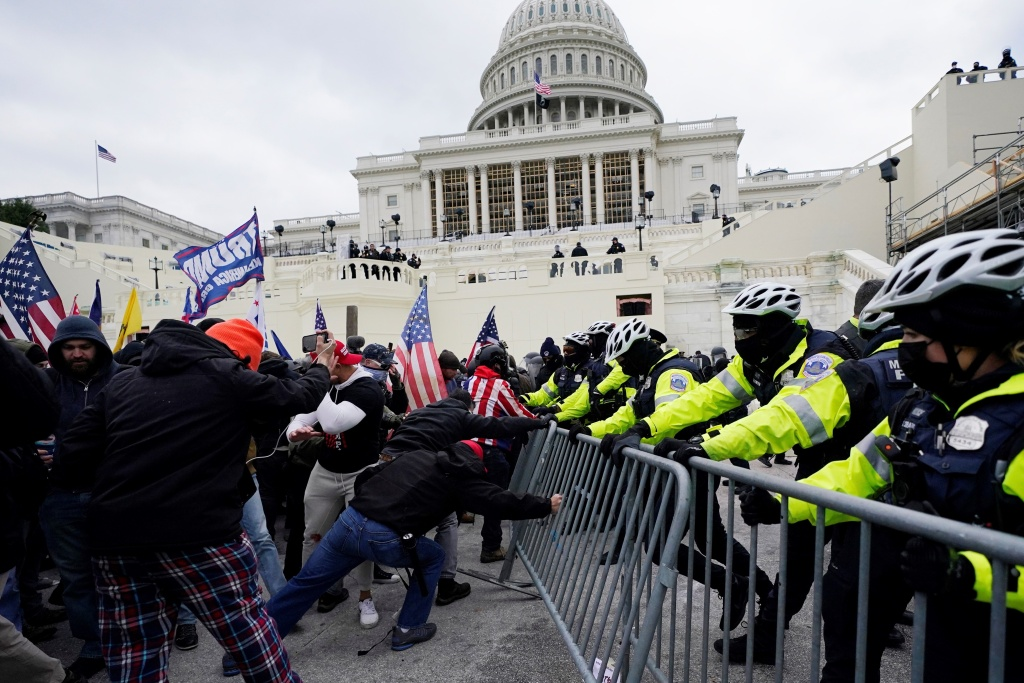 In this Wednesday, Jan. 6, 2021 file photo, Trump supporters try to break through a police barrier at the Capitol in Washington, D.C.