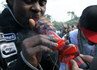 A marijuana user smokes from a bong during a 420 Day celebration on 'Hippie Hill' in Golden Gate Park April 20, 2010 in San Francisco, California.