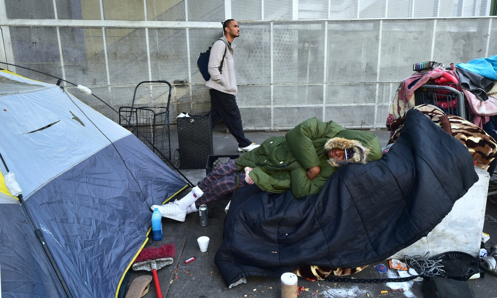 A homeless woman sleeps on a pile of belongings on the street in Los Angeles.