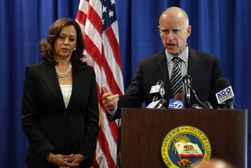 California Attorney General Kamala Harris (L) looks on as California Governor Jerry Brown (R) speaks to reporters after signing the California Homeowner Bill of Rights.