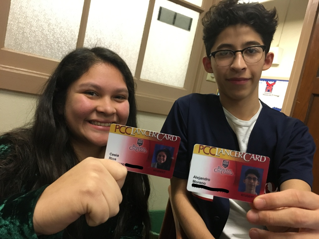 Pasadena high school students Cesia Rios (left) and Alex Moreno hold up college ID cards they received after taking dual enrollment college classes while in high school.