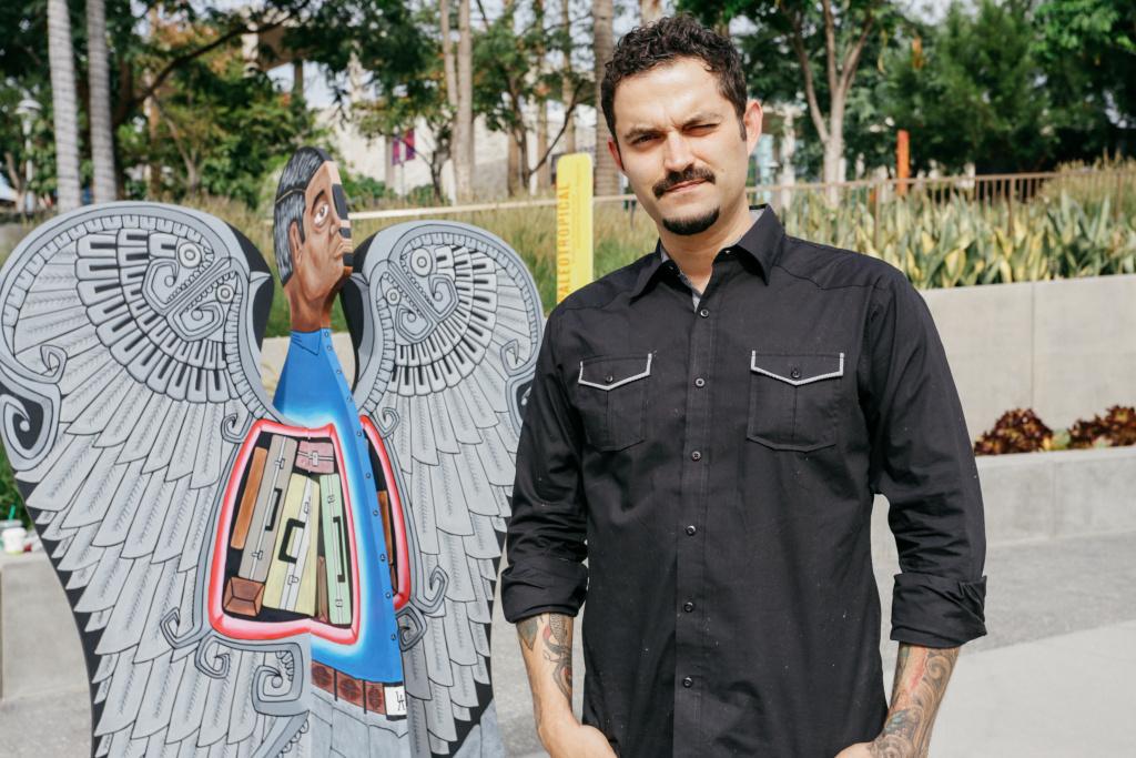 Artist Alvaro Marquez stands next to his angel,