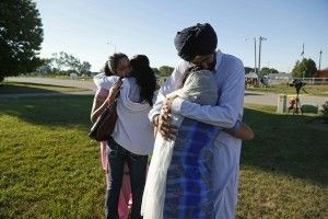Mourners at the scene of Sunday's mass shooting at a Sikh temple in Oak Creek, Wisconsin, August, 6, 2012
