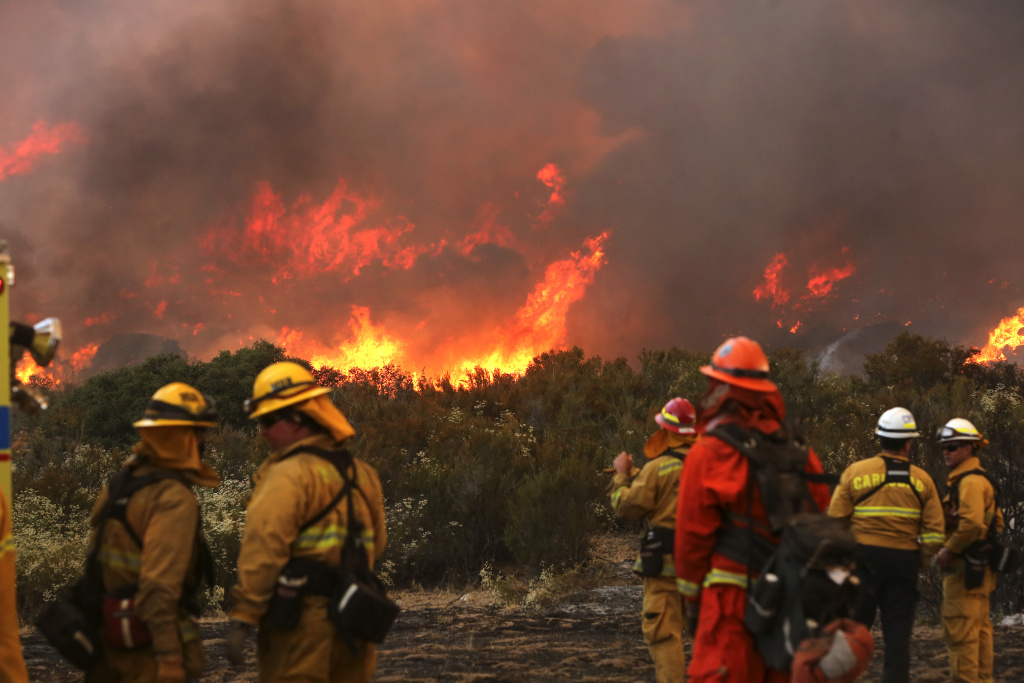 Firefighters watch a backfire flare up at the 6,500 acre Border Fire in eastern San Diego County, California, in the late afternoon on June 22, 2016.