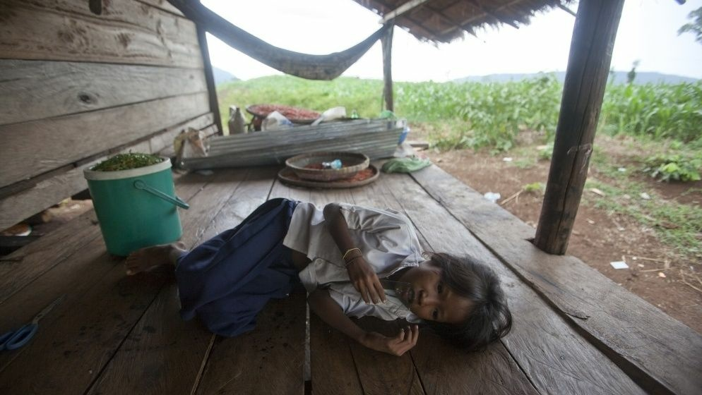 Chhay Meth, 9, suffering through an attack of malaria at the family's home in O'treng village on the outskirts of Pailin, Cambodia, in 2009. A drug-resistant form of malaria in the region medical led officials to declare a health emergency.