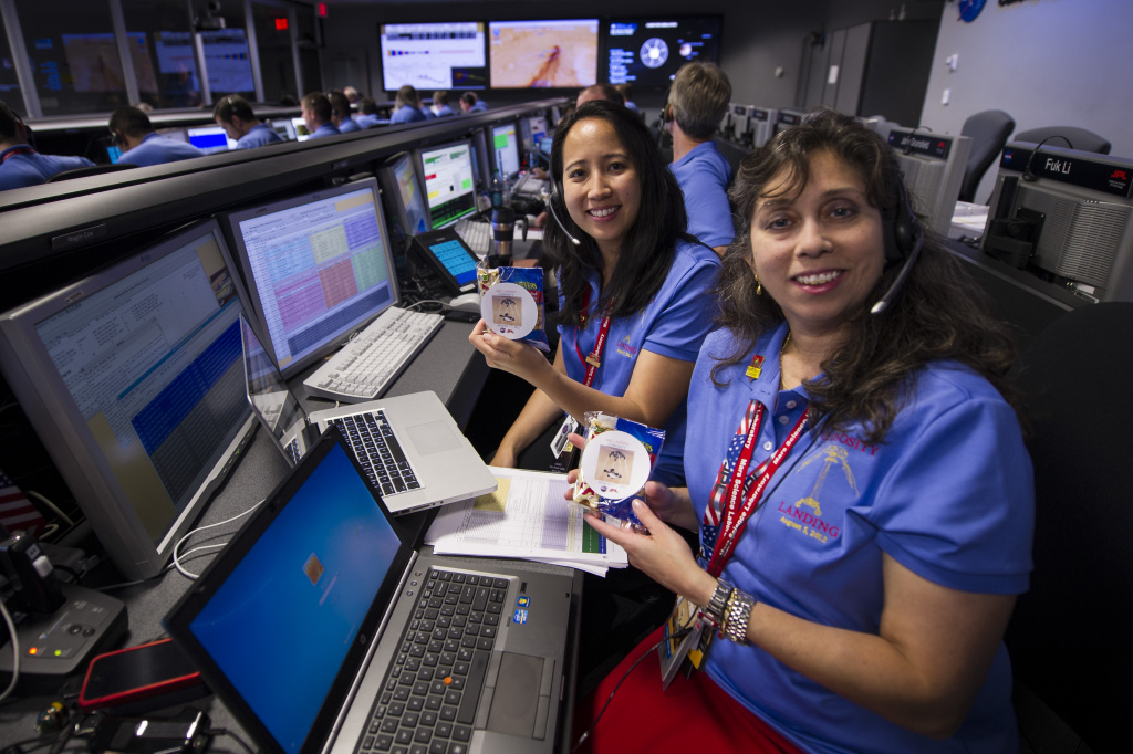 PASADENA, CA - AUGUST 5: In this handout image provided by NASA, Mars Science Laboratory (MSL) Pauline Hwang (L) and Nagin Cox pose for a photograph while holding packs given to each of the team members that contain a mars bar and peanuts in the Mission Support Area at JPL ahead of the planned landing of the Curiosity rover on Mars, August 5, 2012 in Pasadena, California. The MSL Rover named Curiosity was designed to assess whether Mars ever had an environment able to support small life forms called microbes. Curiosity is due to land on Mars at 10:31 p.m. PDT today (1:31 a.m. EDT on Aug. 6, 2012). (Photo by Bill Ingalls/NASA via Getty Images)