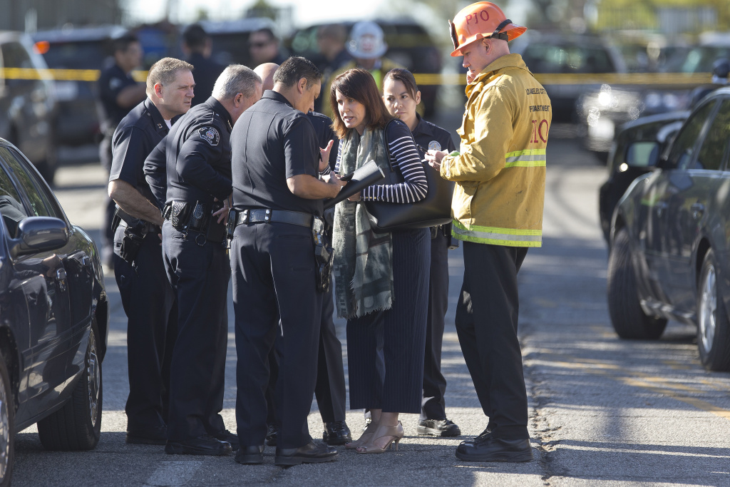 Los Angeles Fire department's Erik Scott, far right, police officers and school officials gather outside the Belmont High School in Los Angeles in this Feb. 1, 2018 file photo. Police say a gun went off a single time in a backpack and the bullet struck two students.