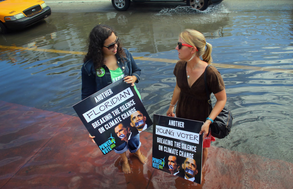 Jacquie Ayala (L) and Amanda Lawrence stand in a flooded street as they and others call on the presidential candidates to talk about their plans to fight climate change on October 18, 2012 in Miami Beach, Florida.  Some of the streets on Miami Beach are flooded due to unusually high tides that the protesters felt are due to rising seas, which are connected to global warming and climate change. Published reports indicate that Florida ranks as the most vulnerable state to sea-level rise, with some 2.4 million people, 1.3 million homes and 107 cities at risk from a four-foot rise in sea levels.