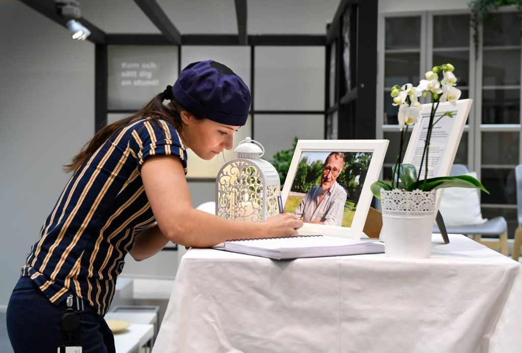 Tove Laxvik, an IKEA employee, signs a book of condolences at the entrance of an IKEA store in Stockholm on January 28, 2018.