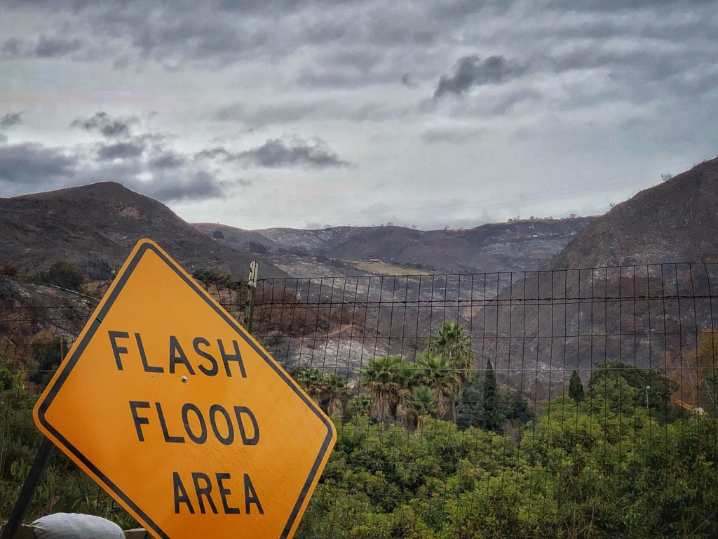 In this photo provided by Santa Barbara County Fire Department, a flash flood area sign is posted, as evacuations have been issued for several fire-ravaged communities in Santa Barbara, Calif., Monday, Jan. 8, 2018.