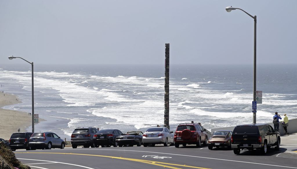 In this photo taken Tuesday, May 14, 2013 cars park for free along Highway 1 above Ocean Beach in San Francisco.