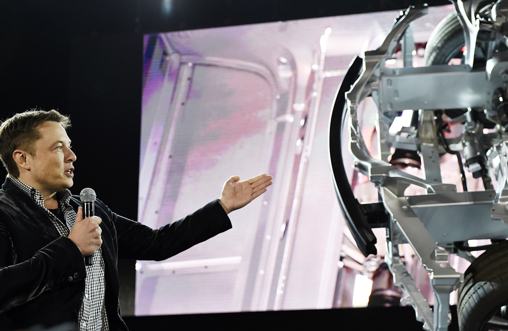 Elon Musk, CEO of Tesla, unveils the dual engine chassis of the new Tesla 'D' model at the Hawthorne Airport October 2014.