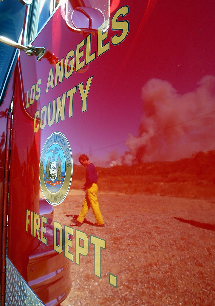 A firefighter and smoke from a huge wildfire are reflected in a Los Angeles County Fire Department fire engine near highway 118 in this file photo taken October 27, 2003 in Simi Valley, California. The county fire department has been under scrutiny recently over evidence of cheating on its admissions exams. Chief Daryl Osby told KPCC on Thursday, March 19, 2015, that several employees could be fired or face other disciplinary action within the next few weeks.
