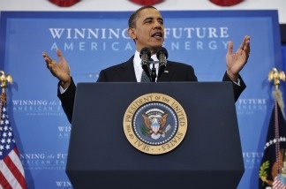 President Barack Obama gestures for the audience to take their seates as he arrives to speak on energy security for the country on March 30, 2011, at Georgetown University in Washington, D.C.
