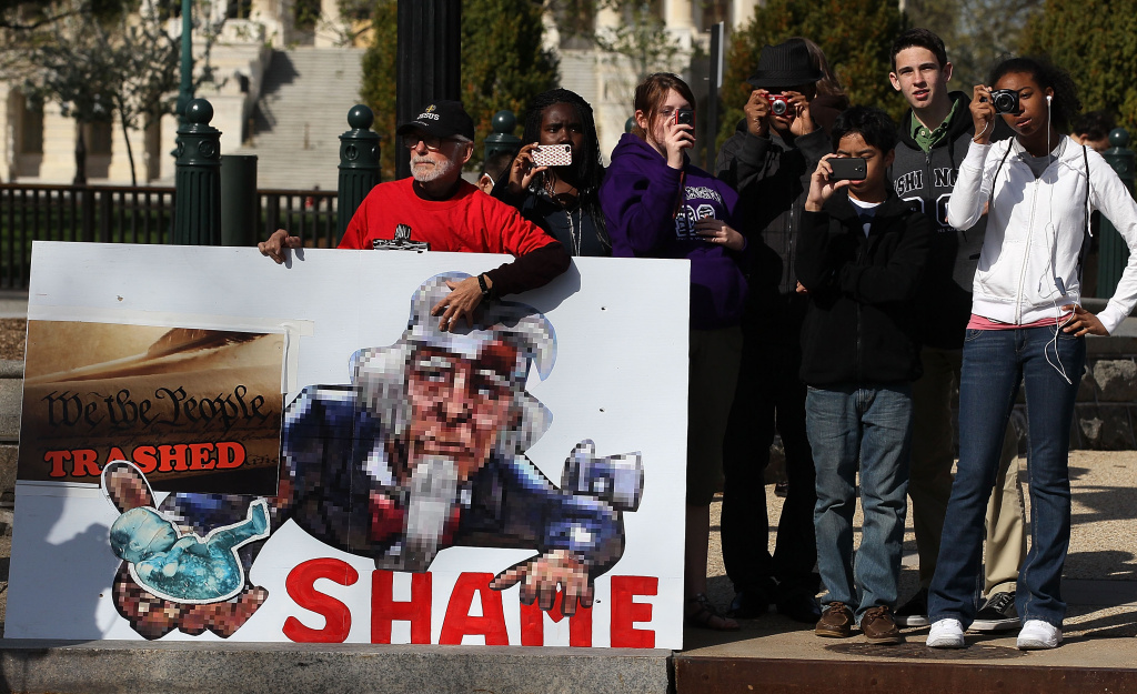 People take pictures as others march in protest of the Patient Protection and Affordable Care Act in front of the U.S. Supreme Court on March 26, 2012.
