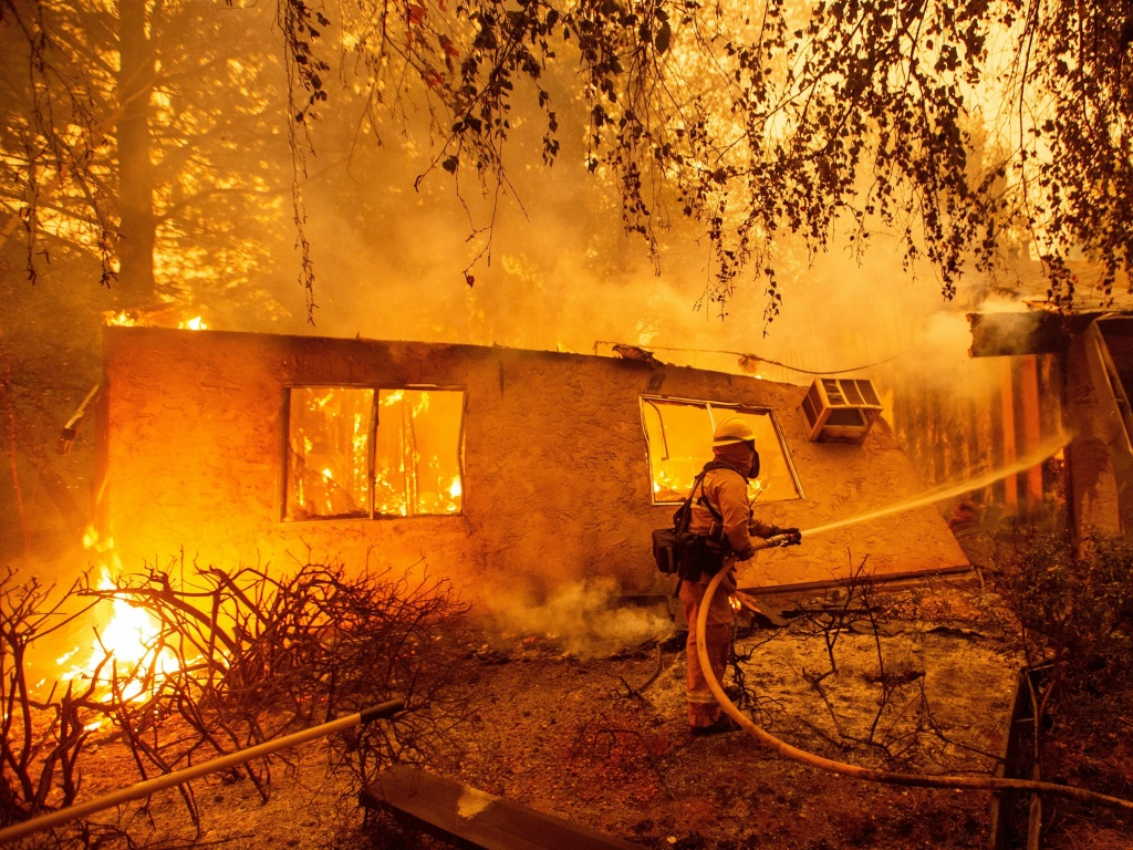 Firefighters battle flames at a burning apartment complex in Paradise, California in November. State fire officials say power lines coming into contact with trees have sparked multiple Northern California wildfires in recent years. PG&E submitted its