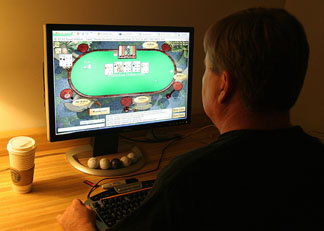 A man plays poker on his computer connected to an internet gaming site from his home in Manassas, VA 02 October, 2006.