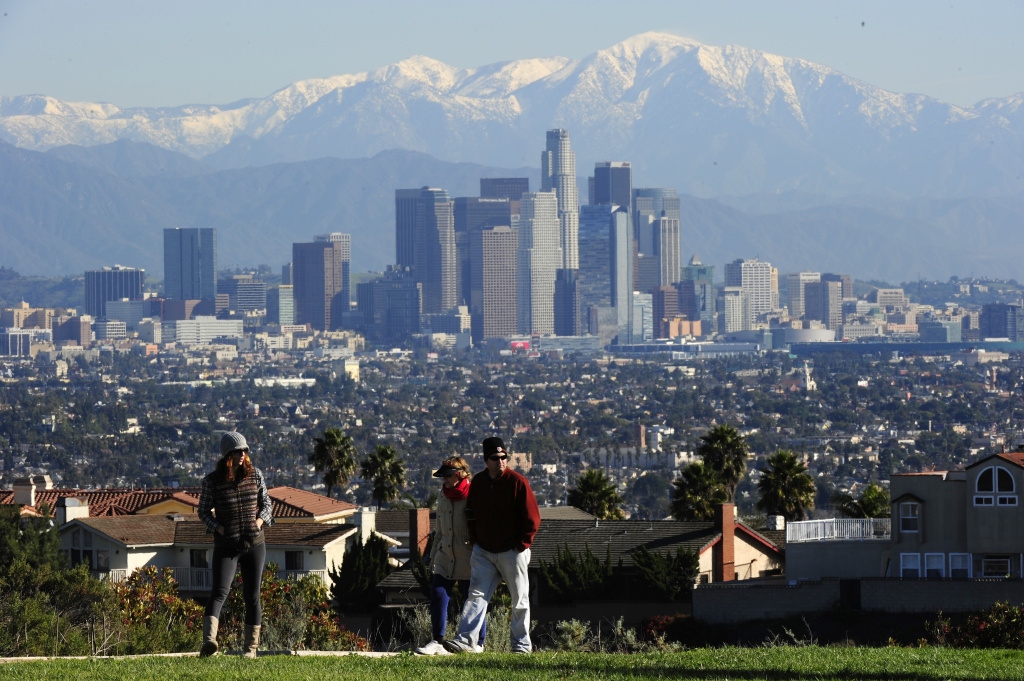 People take a stroll against the background of the Los Angeles city skyline at Kenneth Hahn State Recreation Area on December 31, 2010 in Los Angeles, California.