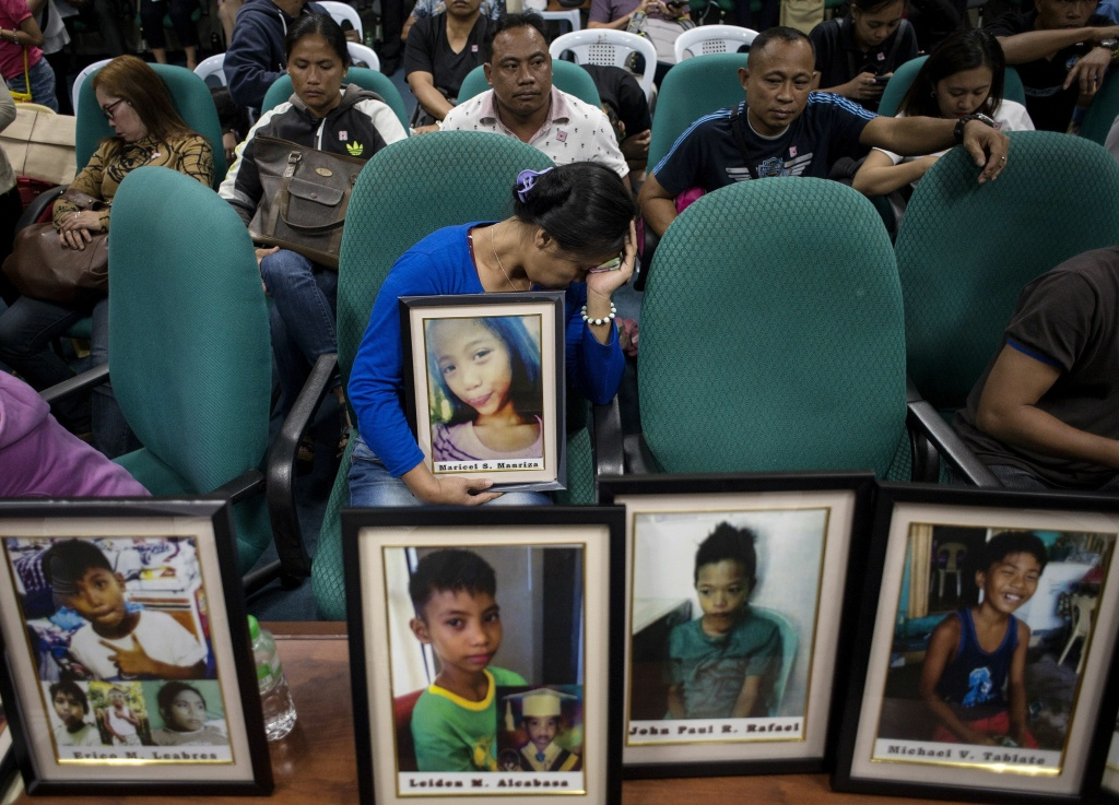 At a senate hearing in Manila on Feb. 21, 2018, on deaths linked to the dengue vaccine, families brought photos of children who had been vaccinated.