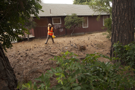 Sue Gordon of Rainbow Environmental Services, current owner of the former Furuta property, walks behind the family's bungalow.