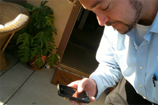 L.A. Unified teacher Daniel Barnhart gets cell phone updates for his trip Thursday to Phoenix to protest SB1070. He's part of a labor union group of several hundred people planning to go for the day.