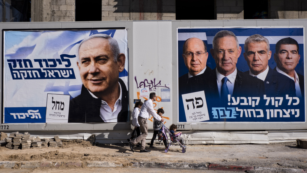 People walk by election campaign billboards showing Israeli Prime Minister and head of the Likud party Benjamin Netanyahu (left) alongside the Blue and White party leaders, including Benny Gantz. Ahead of Tuesday's election, Netanyahu has pledged to annex Israeli settlements in the occupied West Bank.