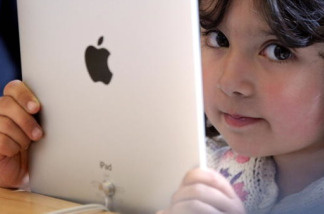 A young girl holds an Apple iPad.