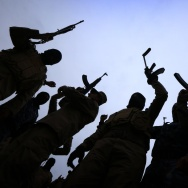 Iraqi policemen raise their weapons during a training session at a camp in the Bardarash district.