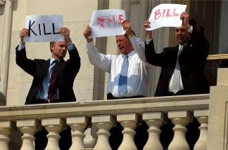 Members of Congress hold up signs from the second floor of the U.S. Capitol that read 'Kill The Bill' on Capitol Hill on March 21, 2010 in Washington, DC.