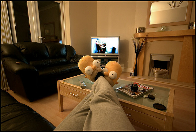 A man watches TV wearing Homer Simpson slippers on February 1, 2008.
