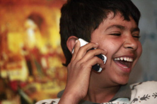 An Iraqi boy laughs as he uses a mobile phone at a shop in Baghdad on March 17, 2008.