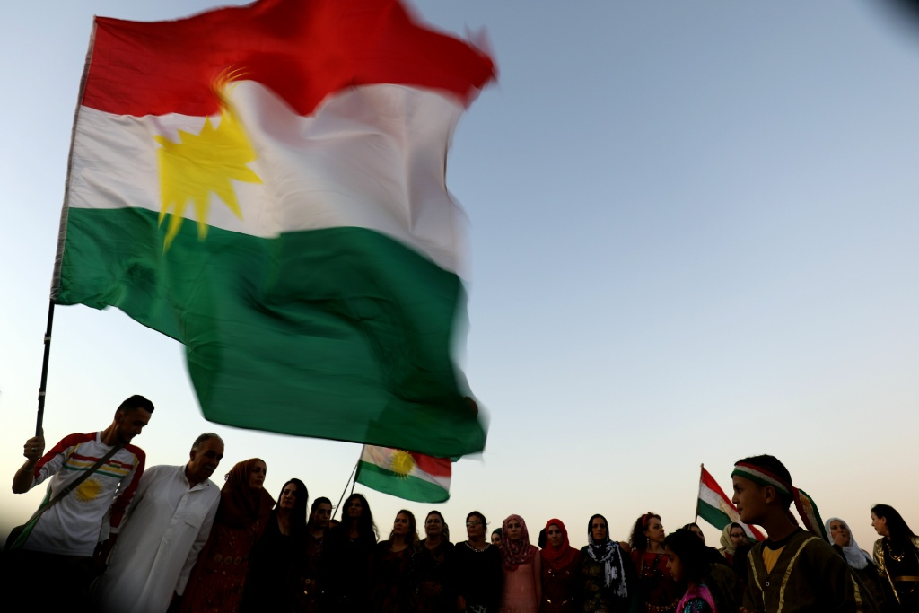 Syrian Kurds wave the Kurdish flag, in the northeastern Syrian city of Qamishli on September 27, 2017.