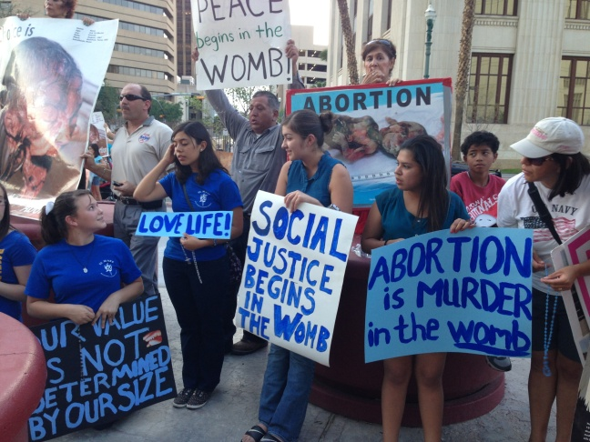 Opponents of the stricter regulations on abortion rally outside the county courthouse in El Paso.