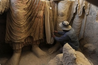 An Afghan archaeologist looks at the remains of Buddha statues discovered inside an ancient monastery in Mes Aynak, in the eastern province of Logar on November 23, 2010.