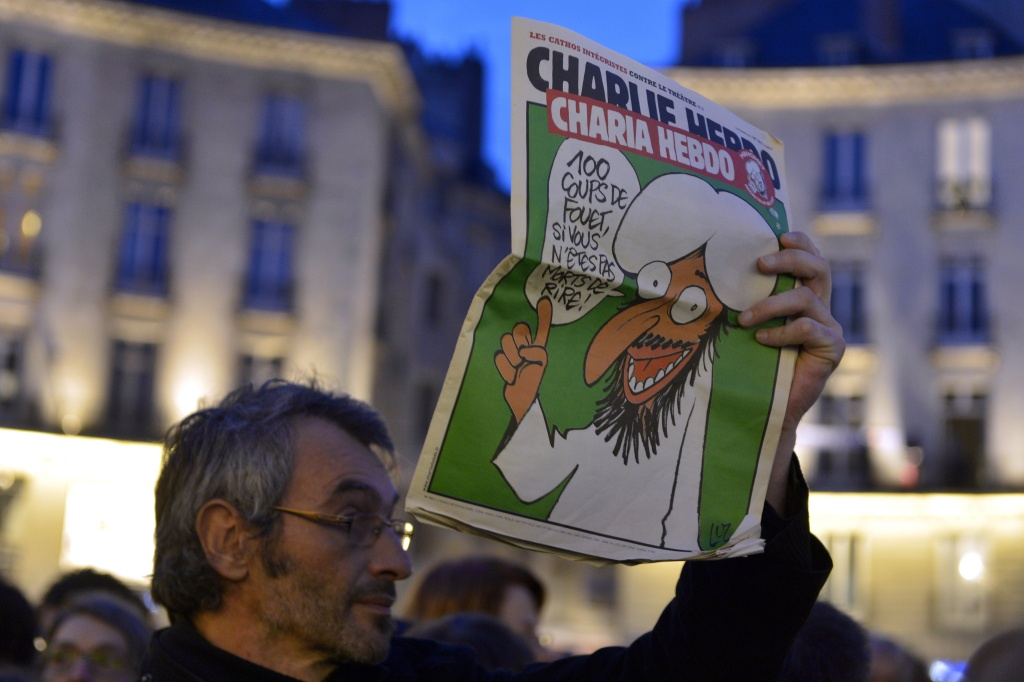 A man holds up a Charlie Hebdo magazine during a rally at the Place Royale in Nantes on January 7, 2015, to show solidarity for the victims of the attack by unknown gunmen on the offices of the satirical weekly, Charlie Hebdo.