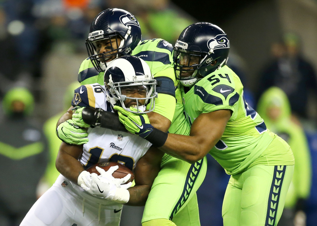 Outside linebacker K.J. Wright #50 of the Seattle Seahawks and middle linebacker Bobby Wagner #54 of the Seattle Seahawks team up to bring down Wide receiver Kenny Britt #18 of the Los Angeles Rams at CenturyLink Field on Dec. 15, 2016 in Seattle, Washington.