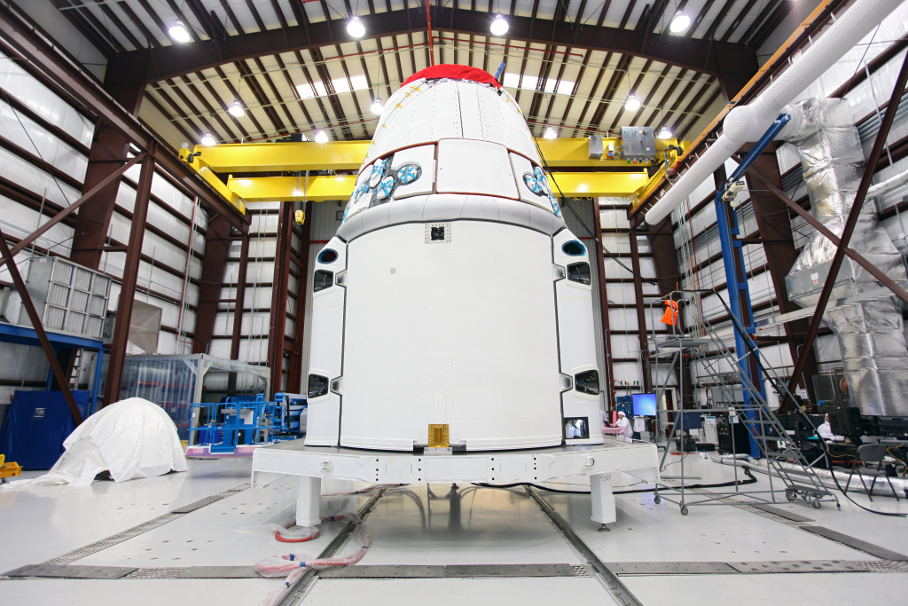 The Dragon spacecraft stands inside a processing hangar at Cape Canaveral Air Force Station where teams had just installed the spacecraft's solar array fairings on Jan. 12, 2013.