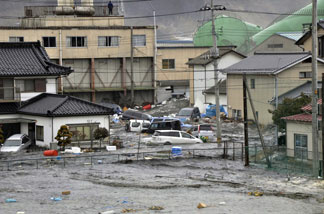 A tsunami, tidal wave smashes vehicles and houses at Kesennuma city in Miyagi prefecture, northern Japan on March 11, 2011.