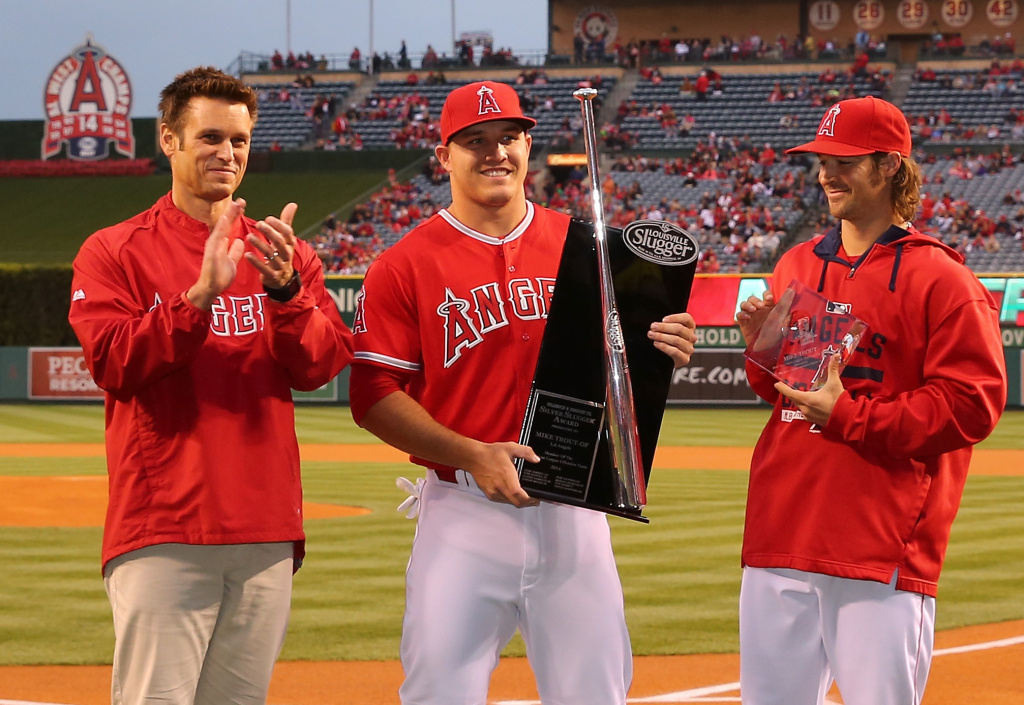 Mike Trout #27 of the Los Angeles Angels of Anaheim is awarded the Silver Slugger Award prior to the MLB game against the Texas Rangers as team General Manager Jerry DiPoto (L) and pitcher C.J. Wilson (R) look on at Angel Stadium of Anaheim on April 24, 2015 in Anaheim, California.