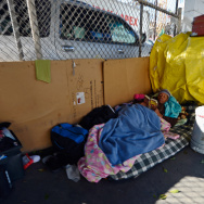 Homeless people from Skid Row are seen on the streets around a construction project where 102 prefabricated housing units placed on top of the second floor of Star Apartments are being built.