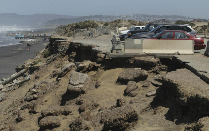 In this May 24, 2012 photo, a man and woman walk in the parking lot at Ocean Beach in San Francisco. In San Francisco, officials are mulling a significant retreat on its western flank, where the Great Highway is under assault from the Pacific Ocean. Right now, a beach parking lot that abuts the highway is crumbing into the sea just across the highway from the San Francisco Zoo.