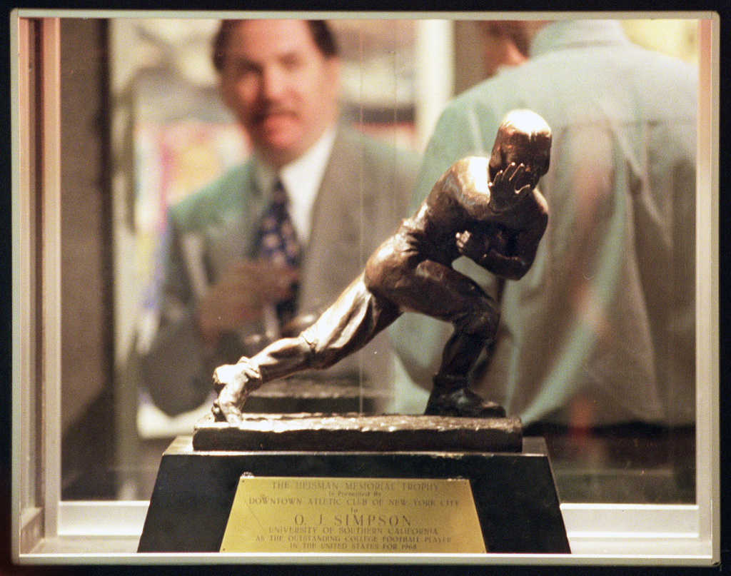 File: Michael Schwartz, director of entertainment memorabilia for the auction house of Butterfield & Butterfield, is seen through a display case containing O.J. Simpson's 1968 Heisman Trophy at their gallery in this Feb. 10, 1999 file photo, in Los Angeles. Los Angeles police say they've recovered a Heisman Trophy honoring O.J. Simpson more than 20 years after it was stolen from the University of Southern California.