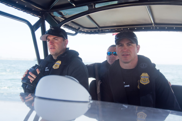 Marine Interdiction agents Bryan Loureiro, left, and Kurt Nagel observe passengers in a boat traveling in the vicinity of the Midnight Express. Many smugglers try to pass as fishermen and the agents on patrol are trained in identifying behavior patterns that could indicate illegal activities.